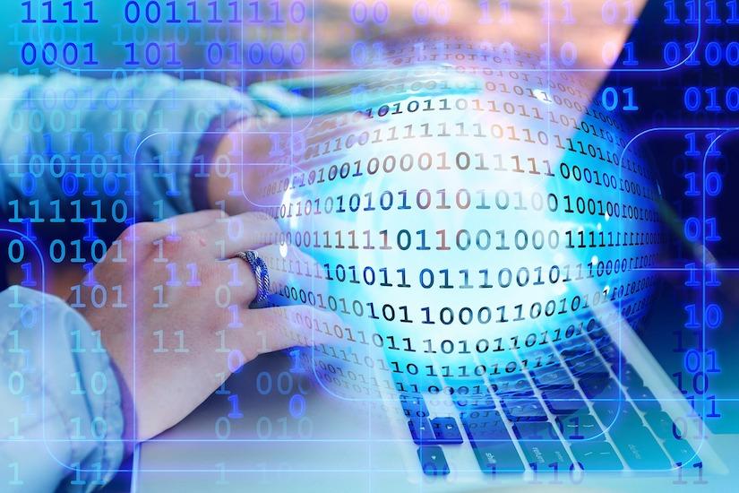Hand auf einer Tastatur vor einer Wolke binärer Zahlen