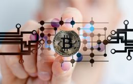 Kryptowährungen - Hand mit Bitcoint in der Hand